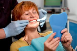 A woman viewing her new dental implants.