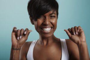 woman smiling flossing her teeth