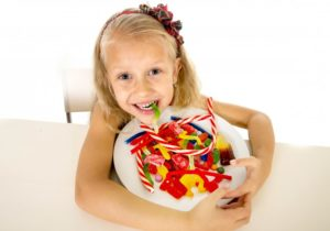 child with a bowl of candy