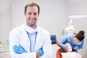 a dentist smiling while a patient has their teeth checked by a dental hygienist