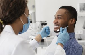 young man smiling at his dentist during a dental cleaning