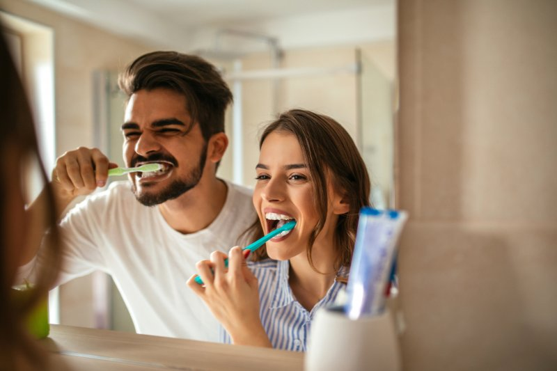 Couple smiling while brushing their teeth