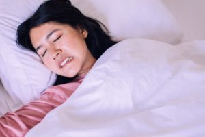 a person grinding and clenching their teeth as they sleep