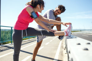 Two runners stretching and smiling on summer day